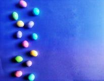 Sucrerie en pastel lumineuse de P?ques sur le fond bleu et pourpre d'ombre photos stock