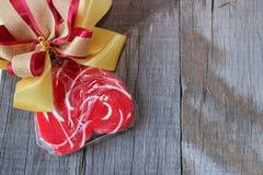 Sucrerie rouge de coeur avec le ruban sur le vieux fond de conseil en bois Concept de jour du ` s de Valentine Photographie stock libre de droits