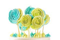 Sucrerie verte et bleue de meringues de lucettes sur le bâton en bois Image libre de droits