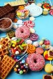 Sucreries avec la gelée et le sucre choix coloré de différents bonbons et festins à childs sur le bleu photographie stock