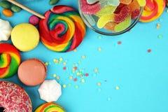 Sucreries avec la gelée et le sucre choix coloré de différents bonbons et festins à childs sur le bleu photos stock