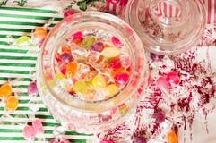 Sucreries colorées dans le pot sur la table image stock