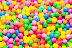 Sucreries colorées et fond coloré de confettis Image stock
