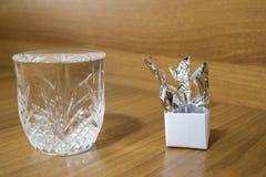 Sucreries dans un récipient de papier et un verre cristal pleins de l'eau o images stock