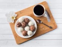 Sucreries de chocolat et de noix de coco dans une cuvette sur une orchidée en bois de tasse de café de plateau Image libre de droits