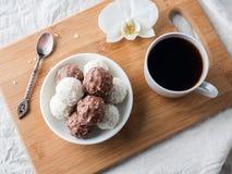 Sucreries de chocolat et de noix de coco dans une cuvette sur une orchidée en bois de tasse de café de plateau Images stock