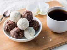 Sucreries de chocolat et de noix de coco dans une cuvette sur une orchidée en bois de tasse de café de plateau Photos stock