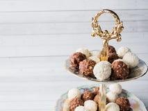 Sucreries de chocolat et de noix de coco dans une cuvette sur une orchidée en bois de tasse de café de plateau Photo libre de droits