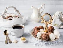 Sucreries de chocolat et de noix de coco dans une cuvette sur une orchidée en bois de tasse de café de plateau Photo stock