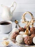 Sucreries de chocolat et de noix de coco dans une cuvette sur une orchidée en bois de tasse de café de plateau Photographie stock