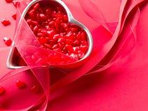 Sucreries de coeur avec des rubans sur le rouge Photos libres de droits