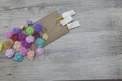 Sucreries de guimauve dans l'enveloppe décorée des roses Présent, surprise, concepts d'amour Photographie stock libre de droits