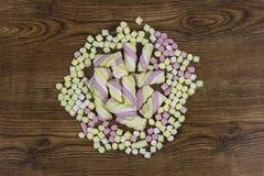 Sucreries de guimauve placées au centre d'autres sucreries Jour du ` s de Valentine et concept d'amour sur le fond en bois Photo libre de droits