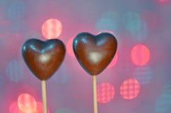 Sucreries en forme de coeur de chocolat sur des bâtons Images stock