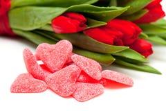 Sucreries en forme de coeur et tulipes rouges photos stock