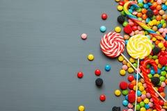 Sucreries et lucettes colorées au-dessus de fond gris Vue supérieure avec l'espace de copie Image stock