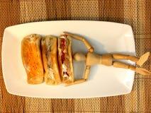 Sucreries et poupée en bois du plat blanc Photo libre de droits