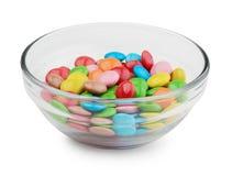 Sucreries multicolores dans le bol en verre d'isolement sur le blanc image libre de droits