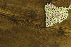 Sucreries placées dans la forme de coeur Jour du ` s de Valentine et concept d'amour sur le fond en bois Photographie stock libre de droits