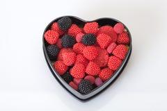 Sucreries rouges dans une boîte en forme de coeur Photo stock
