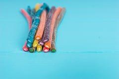 Sucreries savoureuses colorées de réglisse sur le conseil en bois Photographie stock