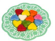 Sucrez les coeurs sur un napperon de dentelle de Livre vert Images stock