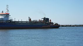 Suction dredger ship entering industrial port on sunny day stock video