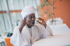 Sudański biznesowy mężczyzna w tradycyjnym stroju używać telefon komórkowego w biurze Zdjęcie Stock