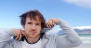 Sudadera con capucha que lleva del hombre en la playa almacen de metraje de vídeo
