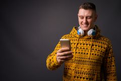 Sudadera con capucha que lleva y auriculares del hombre feliz mientras que usa el teléfono móvil foto de archivo