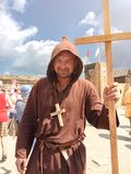 Sudak, Russia - August 16, 2015: man dressed as medieval priest, monk with a wooden cross with a staff in his hand and with a. Sudak, Russia - August 16, 2015 royalty free stock photos