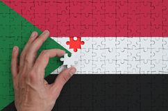 Sudan flag is depicted on a puzzle, which the man`s hand completes to fold.  stock illustration