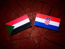 Sudan flagga med den kroatiska flaggan på en isolerad trädstubbe Royaltyfria Bilder