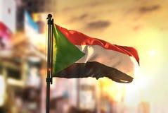 Sudan-Flagge gegen Stadt unscharfen Hintergrund an der Sonnenaufgang-Hintergrundbeleuchtung Stockfoto