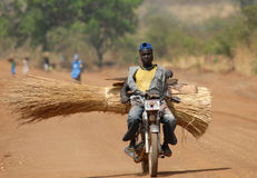 Sudan motorbike. Sudanese man carrying a load of roofing thatch on his motorbike Stock Images