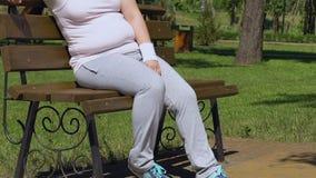 Sudando a la señora gorda que descansa y que restaura la respiración después de entrenamiento agotado en parque metrajes