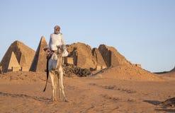 Sudanese man with his camel in a desert near Meroe Pyramids stock photos
