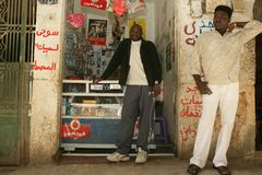 A Sudanese refugee and his friend in front of his mobile phone shop Royalty Free Stock Image