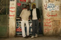 A Sudanese refugee and his friend in front of his mobile phone shop Stock Photography