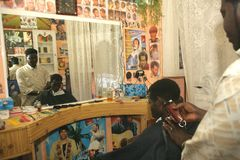 A Sudanese refugee working in a barber shop Royalty Free Stock Image