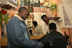 A Sudanese refugee working in a barber shop stock photo