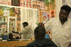 A Sudanese refugee working in a barber shop Stock Images