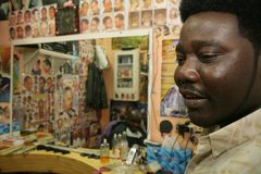 A Sudanese refugee working in a barber shop Royalty Free Stock Photo