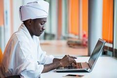 Sudanischer Geschäftsmann in der traditionellen Ausstattung unter Verwendung des Handys im Büro Stockbild