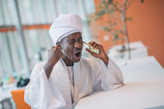 Sudanischer Geschäftsmann in der traditionellen Ausstattung unter Verwendung des Handys im Büro Stockfoto