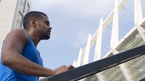 Sudar al atleta de sexo masculino que se coloca en las escaleras, activando para el cuerpo del ajuste, vida activa imagenes de archivo