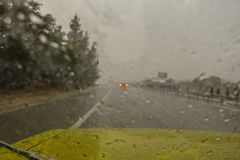 Sudden storm as seen through a windscreen of a car driving along a motorway. Deluge of rain in a sudden strom whilst driving on the motorway. Heavy rain on the stock photo