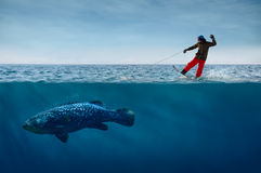Suddenly spring has come. Snowboarder Surfing on Waves with the Fish on a Leash Stock Image