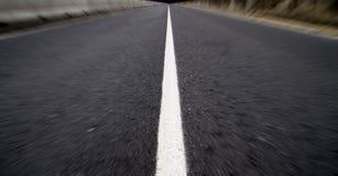 Suddig asfaltväg arkivfoto