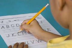 Suddig asiatisk pojkes bokstav L för framsidaspåring Arkivbilder